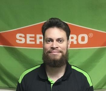 male employee with beard in front of banner
