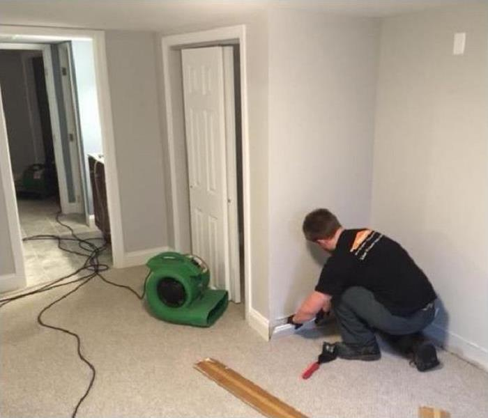 SERVPRO technician removing baseboard in flood damaged room. SERVPRO drying equipment in background