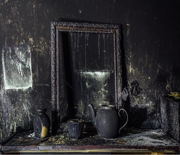 Burnt room with charred wall, picture frame, pot with burned rose in black soot