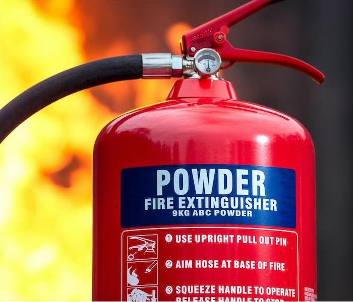 Fire extinguisher top half prominently showing Powder ABC, fire in the background