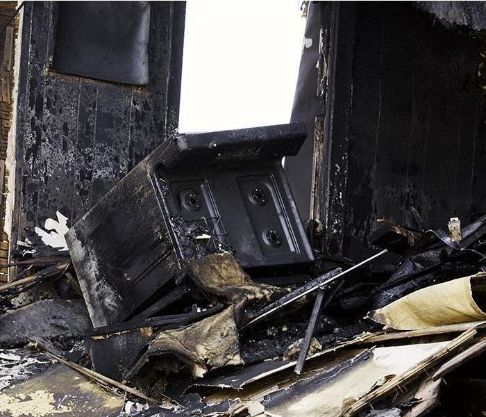 kitchen with stove and walls burned and charred