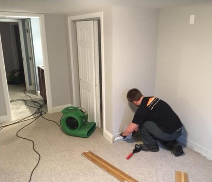 SERVPRO tech removing baseboard in water damaged room; SERVPRO drying equipment being used in room